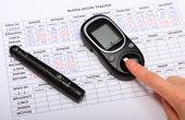 stock photo of diabetes  - Woman doing test for determination level sugar medical form with results of measurement of sugar concept for diabetes - JPG