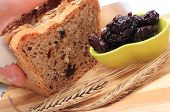 image of fresh slice bread  - Slicing fresh baked wholemeal bread heap of dried plums and ears of wheat lying on cutting board concept for healthy eating - JPG