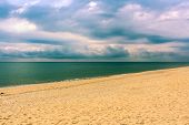 picture of rain cloud  - Lonely deserted sandy beach and leaden rain clouds over the sea. ** Note: Soft Focus at 100%, best at smaller sizes - JPG