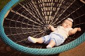 foto of bassinet  - Beautiful baby girl sleeping in a bouncer - JPG