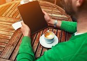 stock photo of screen  - Rear view of male freelancer holding digital tablet with empty screen man sitting at the table with cup of coffee while using touch screen tablet with blank screen student working on tablet pcflare - JPG