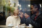 picture of san valentine  - Beautiful couple having lunch view through cafe window dark skinned handsome man feeding his woman with dessert cake at their dating - JPG