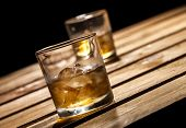 stock photo of scotch  - Glasses of scotch on wooden and black background with copyspace - JPG