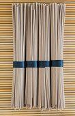foto of bundle  - bundles of buckwheat soba noodles on bamboo background - JPG