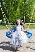 foto of polite girl  - Pretty girl in a princess dress swings - JPG