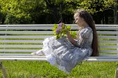 picture of polite girl  - Little girl on a bench holding flowers - JPG