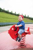 picture of playground  - child with hat on playground spring fish - JPG