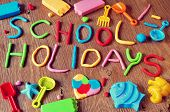 stock photo of molding clay  - the text school holidays made from modelling clay of different colors and some beach toys such as toy shovels and sand moulds - JPG