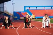 stock photo of race track  - business woman in start position ready to run and sprint on athletics racing track - JPG