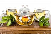 stock photo of teapot  - still life of the glass teapot flow green tea in cup on wooden trivet white background isolated tea ceremony - JPG