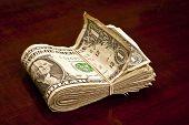 image of bundle  - Bundle of worn folded dollar bills on a wood counter top - JPG