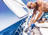 picture of work crew  - Handsome shirtless sailor working on sailboat - JPG