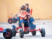 stock photo of pedal  - happy boy child riding a pedal cart - JPG