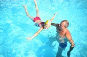 stock photo of grandpa  - Grandpa teaches granddaughter to swim in the swimming pool - JPG