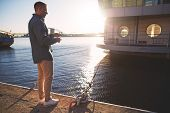 pic of street-rod  - Man casting with light rod on the river near the dock - JPG