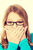picture of shame  - Teenage woman covering mouth because of shame - JPG