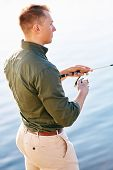 foto of street-rod  - Man casting with light rod on the river against the water surface - JPG