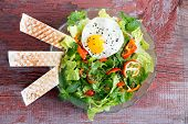 stock photo of leafy  - Fresh leafy green mixed salad with lettuce and herbs tomato and sweet bell peppers served with a seasoned fried egg and wafers viewed from above on a rustic wooden table - JPG