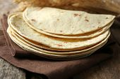 foto of whole-wheat  - Stack of homemade whole wheat flour tortilla on napkin - JPG