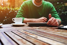 picture of coffee coffee plant  - Front view young man sitting at the table with cup of coffee digital tablet and smart phone man - JPG
