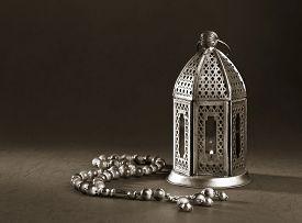 foto of monochromatic  - A metallic Ramadan lamp with Islamic rosary beads on black background - JPG