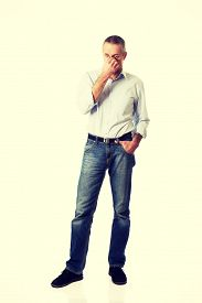 picture of sinuses  - Mature man holding his nose because of sinus pain - JPG