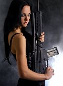 Sexy woman with weapon on smoky background