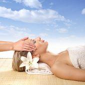 Attractive woman getting spa treatment iver sky background