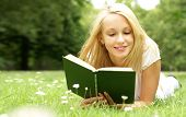 pic of girl reading book  - Young beautiful girl reading a book outdoor - JPG
