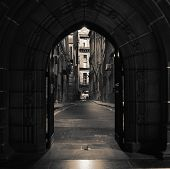 stock photo of derelict  - Looking through arched doors in ancient building towards empty alleyway - JPG