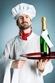 Portrait of a man cook holding a bottle of champagne. Shot in a studio over grey background.