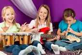Children �¢�?�? sisters - making music; they are practicing playing guitar, bongo and flute