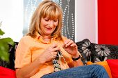 Woman is knitting in her living room for relaxation