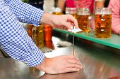 Waiter �¢�?�? only hands to be seen - in a Bavarian pub taking orders
