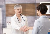 Senior doctor shaking hand with patient in office.?