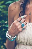 closeup of young woman hand with  lot of boho style jewrly, rings and bracelets outdoor summer day poster