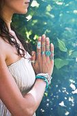 close up of yoga woman hands in namaste gesture with lot of boho style jewelry rings and bracelets o poster