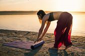 Woman On The Beach At Sunset Starts Yoga Training With Yoga Mat. Morning Natural Stretch Warm-up Tra poster
