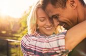 Young couple embracing at park during sunset. Closeup of cheerful boyfriend and girlfriend hugging o poster