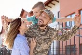 Male Soldier Reunited With His Family Outdoors. Military Service poster