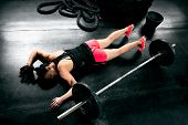 Tired Woman After Hard Training Lying Near Weights poster