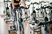 Feet Of An Attractive Young Girl Training On Bike In Gym. Fitness Woman On Bicycle Doing Spinning At poster