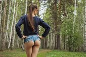 Crop Back View Of Fit Anonymous Female In Provocatively Denim Shorts With Long Hair Posing In Wood poster