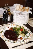 Elegant Restaurant Plate With A Big Steak And Gravy Garnished With Steamed Vegetables.