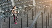 Happy Girl At Morning Cardio Workout. Young Sporty Woman With Smartphone Choosing Playlist For Train poster