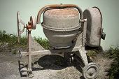 Rarely Used Cement Mixer Standing Near Wall. Cement Mixers, Or Concrete Mixers, Allow Users To Mix L poster
