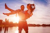 Young Man Holding Woman Running On Summer River Bank. Couple In Love Having Fun At Sunset. Guys Chil poster