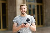 Staying In Touch. Send Message Concept. Man With Beard Walks With Smartphone, Urban Background. Guy  poster