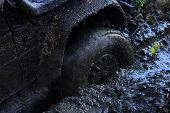 Wheel With Little Cloud Of Smoke, Defocused. Fragfment Of Car Stuck In Dirt, Close Up. Dirty Offroad poster