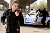 Young Attractive Policewoman Using Walkie-talkie With Blurred Partner Near Car On Background poster